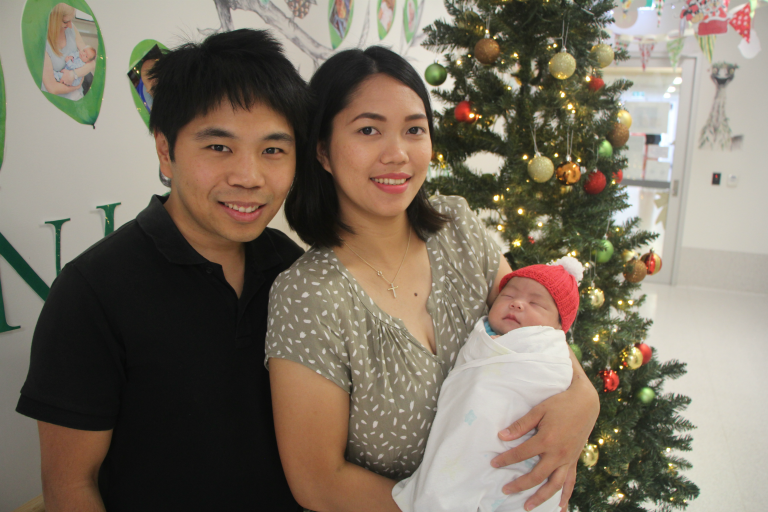 Father and mother holding newborn next to Christmas tree