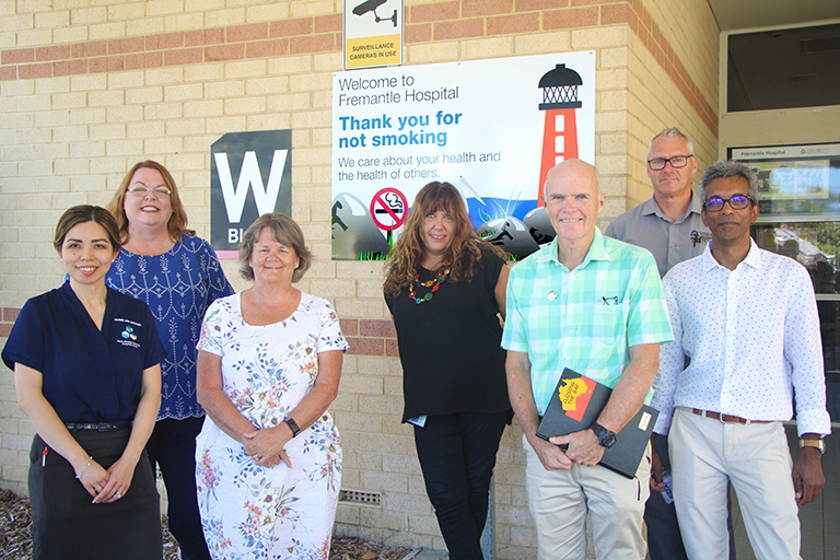 Four women and three men stand in front of a sign on a wall that reads 'Welcome to Fremantle Hospital - Thank you for not smoking'