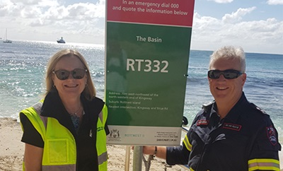 Two people stand beside a beach emergency number (BEN) sign. The sign features specific location advice in the event of an emergency.