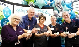 Five Fiona Stanley HOspital staff members each holding a cupcake with a candle on top