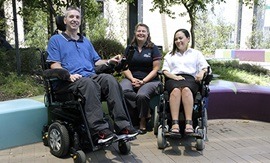 A man and woman, both seated in wheelchairs, in an outdoor courtyard. Another women sits with them on a brightly coloured seat.