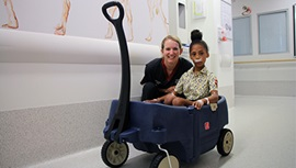 A young female nurse sits next to a young female hospital patient who is seated in a colourful toy cart.
