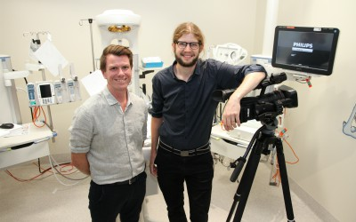 Consultant Neonatologist Rory Trawber and Clinical Videographer Jason Janetzky standing next to a video camera and screen
