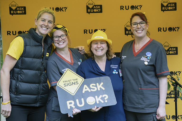 Four woman stand in front of a yellow banner that reads RUOK? One of the women holds a sign that reads Ask RUOK?