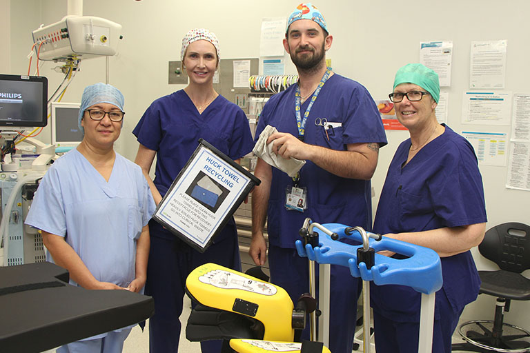 Three women and a man wearing surgical scrubs stand in an operating theatre.