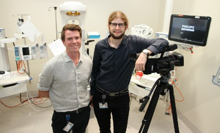 Consultant Neonatologist Rory Trawber and Clinical Videographer Jason Janetzky standing next to a video camera and monitor
