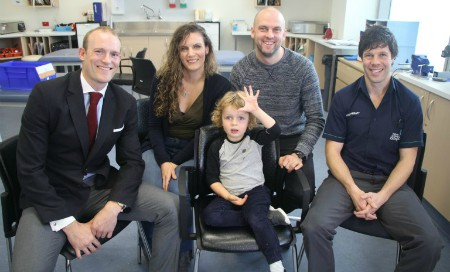 Doctor, mother, father and physiotherapist sit around boy holding his hand in the air
