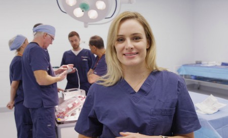 Surgeon in scrubs standing in theatre with team of medical staff in the background