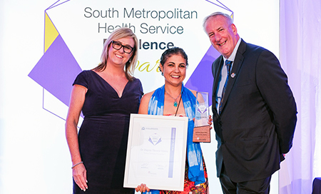 Two women and a man stand in front of a banner that reads South Metropolitan Health Service Excellence Awards. One woman holds a framed certificate.