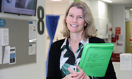 A woman standing in a medical treatment area holding a folder
