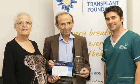 Man and woman hold award standing next to Fiona Stanley Hospital clinician