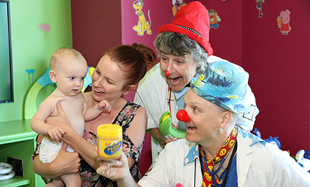 A woman holds a young baby. A man and woman dressed as clown doctors are standing next to them