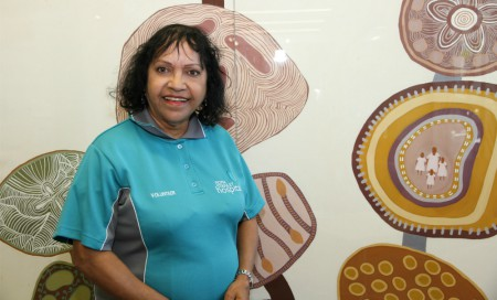 FSH volunteer Marie Rawson standing in front of some Aboriginal art