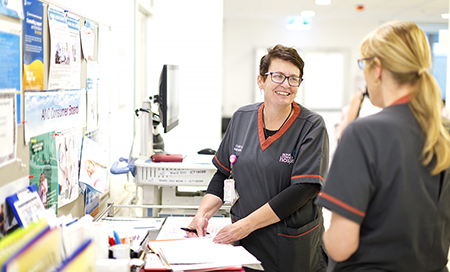 Two female midwives in conversation.