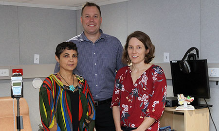 A man and two women standing in a treatment room